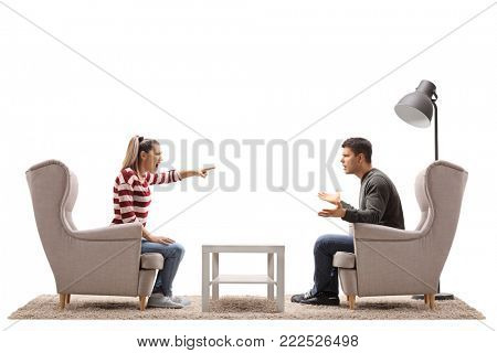 Young couple seated in armchairs having an argument isolated on white background