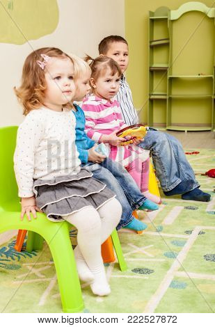 Children in the kindergarten sitting on the chairs and listen something