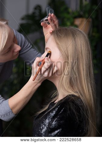 make-up artist doing make-up of a young beautiful blond woman at home.
