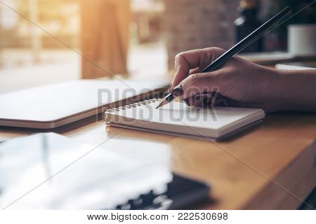 Closeup image of woman's hand writing on a blank notebook with laptop , tablet and coffee cup on wooden table background