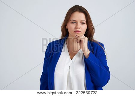 Portrait of pensive woman holding hand on chin and looking thoughtful