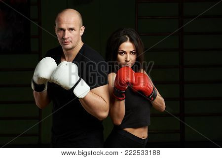 Boxing lessons concept. Young woman and man hold hands up in boxing gloves