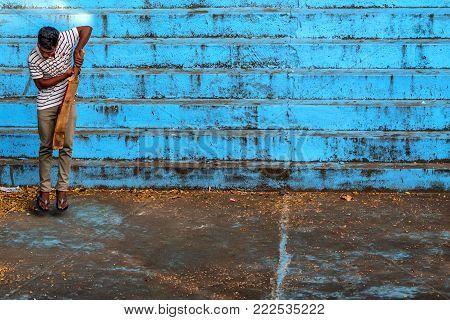 BENTOTA, SRI LANKA - CIRCA DECEMBER 2016: Local Sri Lankan man plays cricket outdoors. Cricket is a popular game in Sri Lanka.
