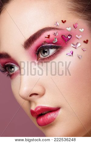 Face of Beautiful Woman with Holiday Makeup Heart. Valentine's Day Make-up. Lips in Pink Lipstick. Makeup detail. Face of Girl on a Pink Background