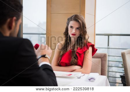 partial view of woman looking at boyfriend with gift at restaurant on st valentine day