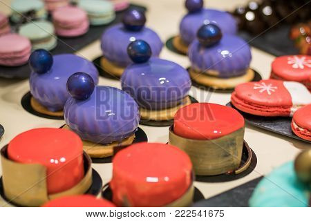 Colorful icing on the cakes. Modern French mousse desserts with mirror glaze. Picture for a menu or a confectionery catalog.