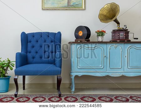 Vintage interior of retro blue armchair, vintage wooden light blue sideboard, old phonograph (gramophone), vinyl records on background of beige wall, tiled porcelain floor, and red carpet