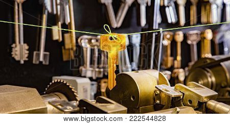 Golden key on a green twine in a locksmith workshop. Close up..