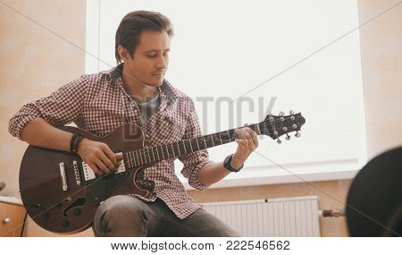 Young guy musician composes music on the guitar and plays in the kitchen, close up shot