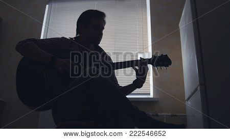 Dark silhouette of young attractive man musician composes music on the guitar and plays, silhouette - close up