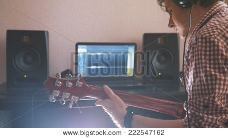 Young musician composes and records music playing the electric guitar, using computer and keyboard, from the front view