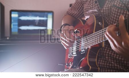 Young male musician composes and records soundtrack playing the guitar, using computer, focus on hands and equipment