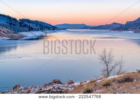 calm winter dusk over partially frozen Horsetooth Reservoir near Fort Collins in northern Colorado