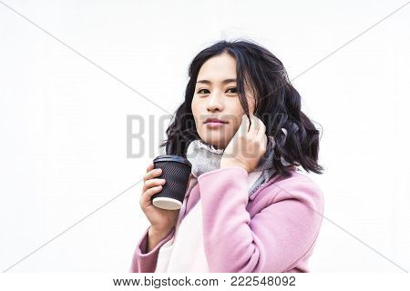 Beautiful young asian woman drinking hot drink from disposable paper cup outdoors on white background. Look at the camera. Girl dressed in pink coat and white scarf.