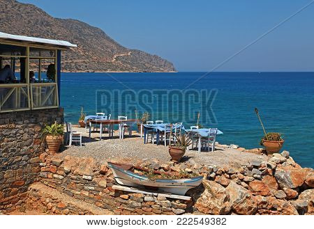 Landscape with traditional greek tavern with tables and chairs on rock coast overlooking Mediterranean sea, Crete, Greece.