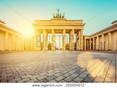 Famous Brandenburger Tor (Brandenburg Gate), one of the best-known landmarks and national symbols of Germany, in beautiful golden morning light at sunrise with lens flare effect, Berlin, Germany