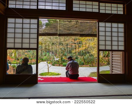 Kyoto, Japan - Nov 29, 2016. People sitting at a traditional house and looking at autumn garden in Kyoto, Japan.