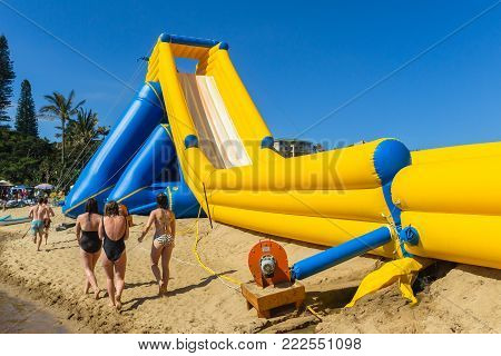 Teen girls boys caucasian thrill rides down high water slide inflated amusement structure on beach summer holidays.