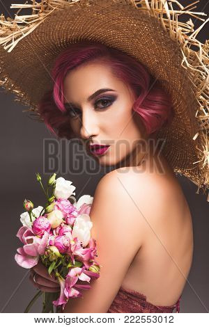 pretty pink haired girl in straw hat posing with flowers infront of grey background