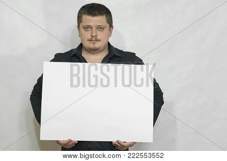 A man is holding an empty scoreboard or white square of paper. Face seriously. On a white background. copyspace