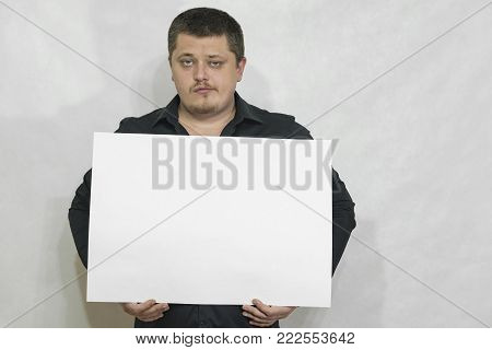 A man is holding an empty scoreboard with copyspace. On a white background. copyspace