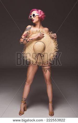 attractive naked pin up girl in sunglasses covering by straw hat infront of grey background