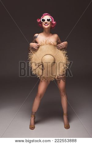 beautiful naked pink haired woman in sunglasses covering by straw hat infront of grey background