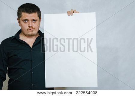 A man is holding a white square of paper or scoreboard. On a white background.