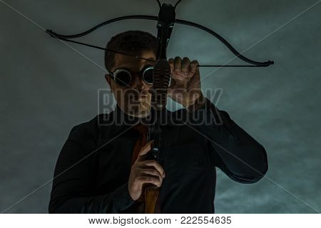 The arboleth in the hands of the young man is pointing upwards. Dark camouflage glasses. A man's hand pulls a string of arbollet.