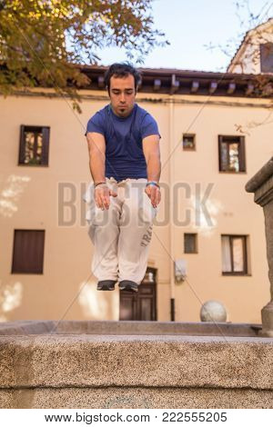 Young man doing a parkour jump on the street.