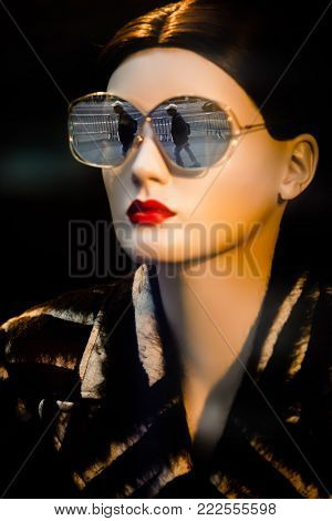 NEW YORK, USA - Sep 16, 2017: Mannequins wearing fashion sunglasses in a shop window in Manhattan. The figure of a man is reflected in glasses