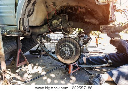 Technician are repairing the front and undercarriage crashes from the accident on the road parked in the garage. Concept for the automotive industry and insurance.