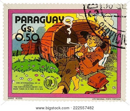 Moscow, Russia - January 18, 2018: A stamp printed in Paraguay shows Huckleberry Finn in the old barrel, Adventures of Tom Sawyer by Mark Twain, series
