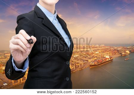 Smart business woman holds a marker writing in air with shipping boat at shipping yard in background.Photo design with copy space for Global business containers shipping and logistic concept.