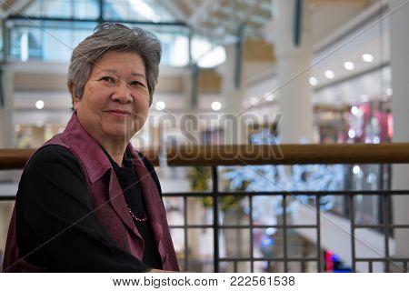 elder senoir smiling in department store. happy elderly woman sitting at cafe coffee shop or restaurant.