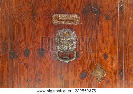 Old iron door handle on a wooden door. Old Iron Door Handle.