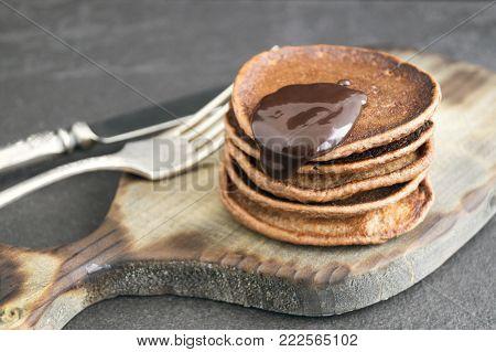 Chocolate Pancakes With Chocolate Sauce On A Dark Background.