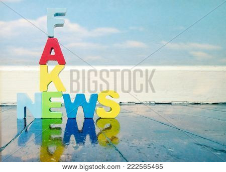 Fack News ,wooden letters on old wooden floor with reflection
