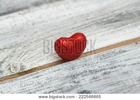 The Red Shinny Heart Lies on the Crack of the Wooden Background.