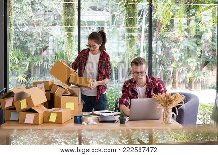 Startup Small Business Owner Working With Computer At Workplace. Freelance Man & Woman Seller Check