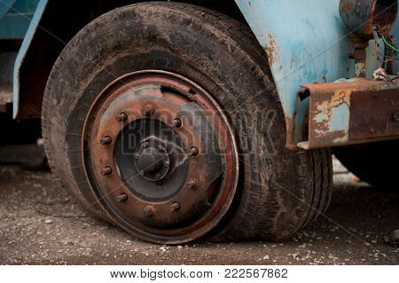 Old ruined truck tire, flat tire on rusted wheel