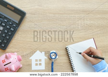 Top view of hand writing about hourse insurance concept with stethoscope, house paper, piggy bank, calculator and notepad