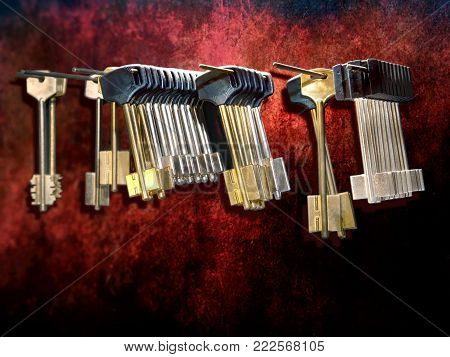 Many various blank  keys on a red wall in a locksmith workshop. Close up..