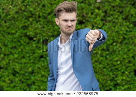 Businessman in blue shirt showing thumb down, disappointed, dislike, disagree the suggestion