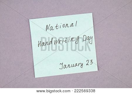 A note with an inscription is a national day of hand writing and a pen on a gray background