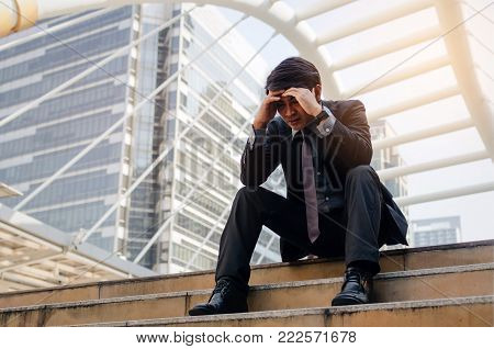 disappointed, sadness or stressed medium aged unemployed business man with briefcase sitting on walkway in the city after fired from job, business problem, unemployment, financial, investment concept