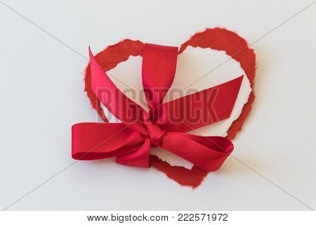 Close view of red and white paper valentine hearts tied together with red satin bow, isolated on white, horizontal aspect
