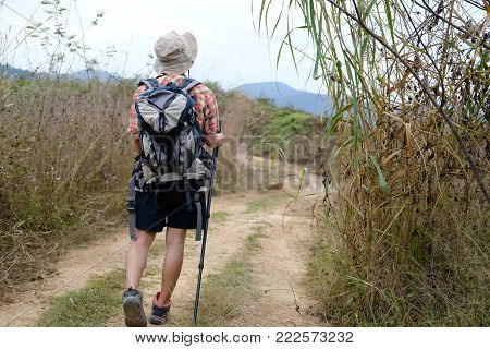 Traveler Hiker Man With Backpack Hiking On Mountain. Leg Of Tourist Backpacker With Stick Trekking I
