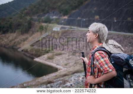 traveler hiker man with backpack hiking near lake. tourist backpacker with stick trekking in the evening. travel lifestyle & summer vacation concept