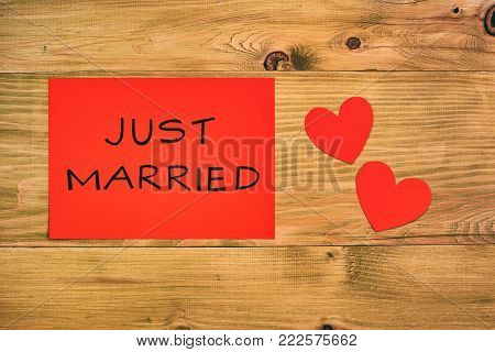 Image of text on red paper  just married with hearts  on wooden table